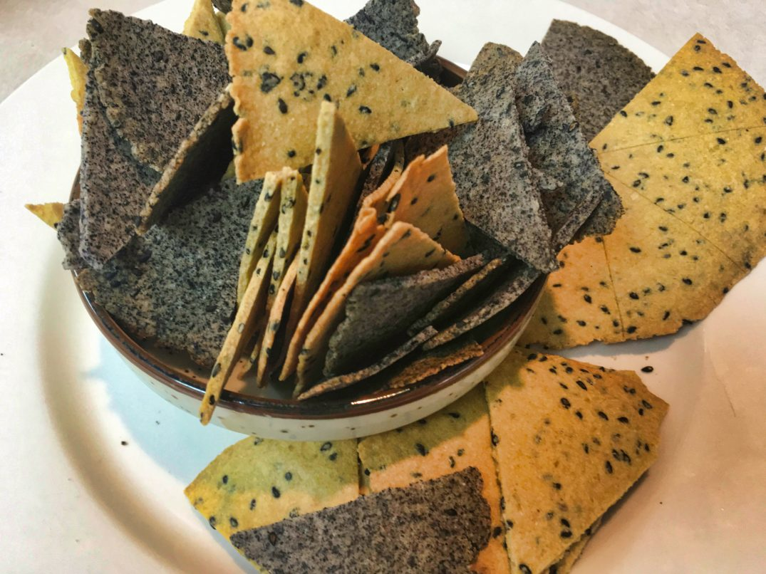 A bowl of baked chick pea flour and black bean flour crackers